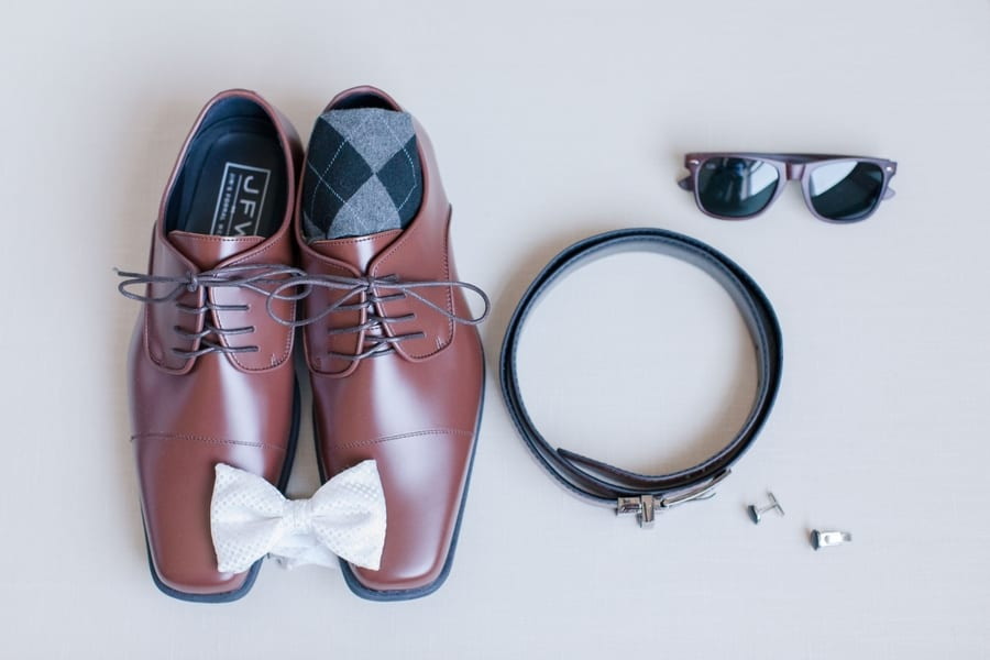 close up of grooms accessories of brown shoes and white bow tie, belt, cufflinks and sunglasses