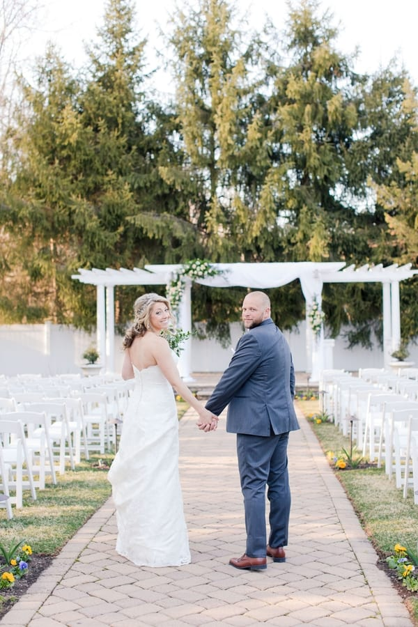 bride and groom on aisle of outdoor ceremony location holding hands looking back at the camera
