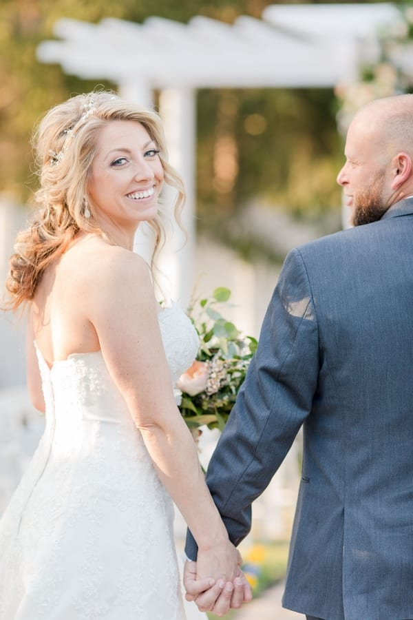 photo of bride and groom from behind with bride looking back over her right shoulder