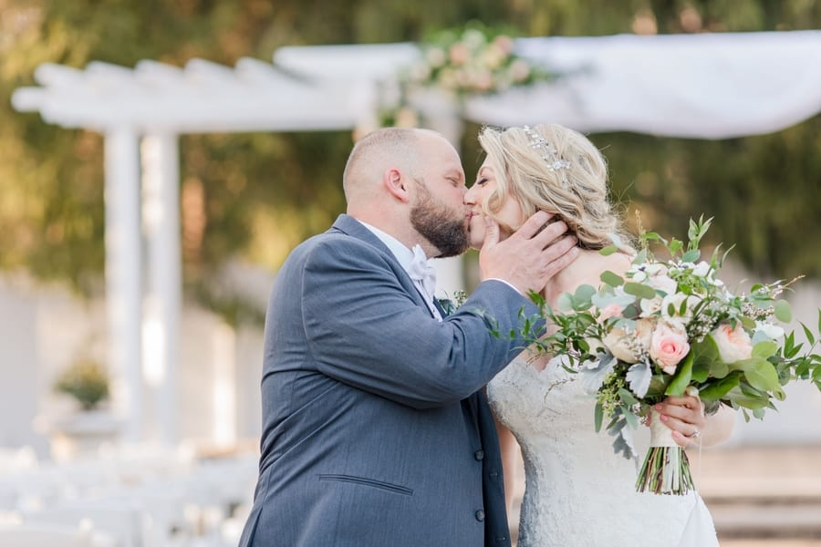 bride and groom portrait outdoors, kissing each other while holding bouquet