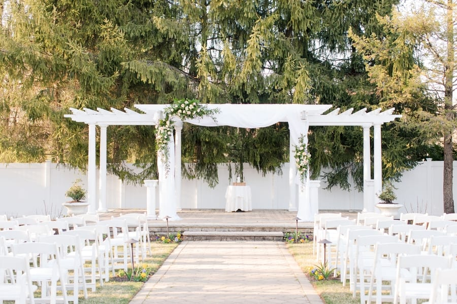 wide angle shot of ceremony location of white chairs, white pergola decorated in white fabric with greenery and peach florals in top left corner of perola and right column