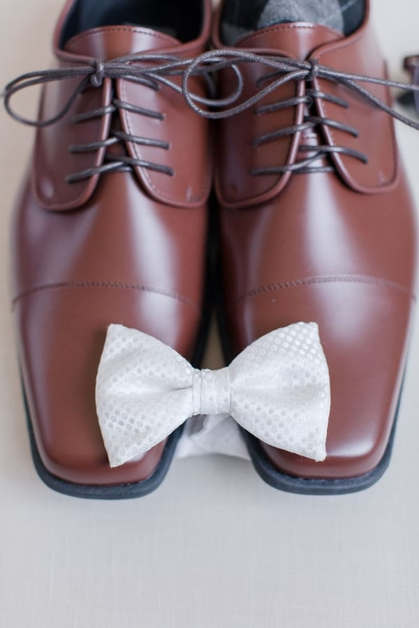 close up of grooms accessories of brown shoes and white bow tie