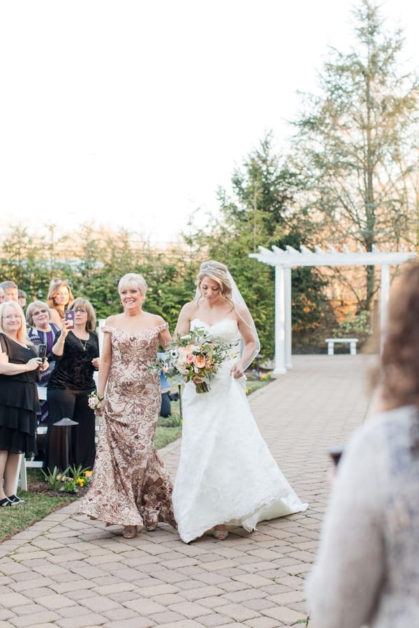 bride being walked down the aisle by her mother