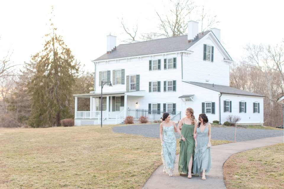 three bridesmaids in blues and greens walking down the path at Updike Farmstead in front of main house
