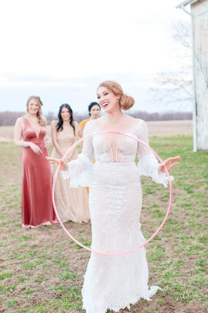 bride in lace illusion bridal gown playfully holding a hula hoop while her three bridesmaids look on