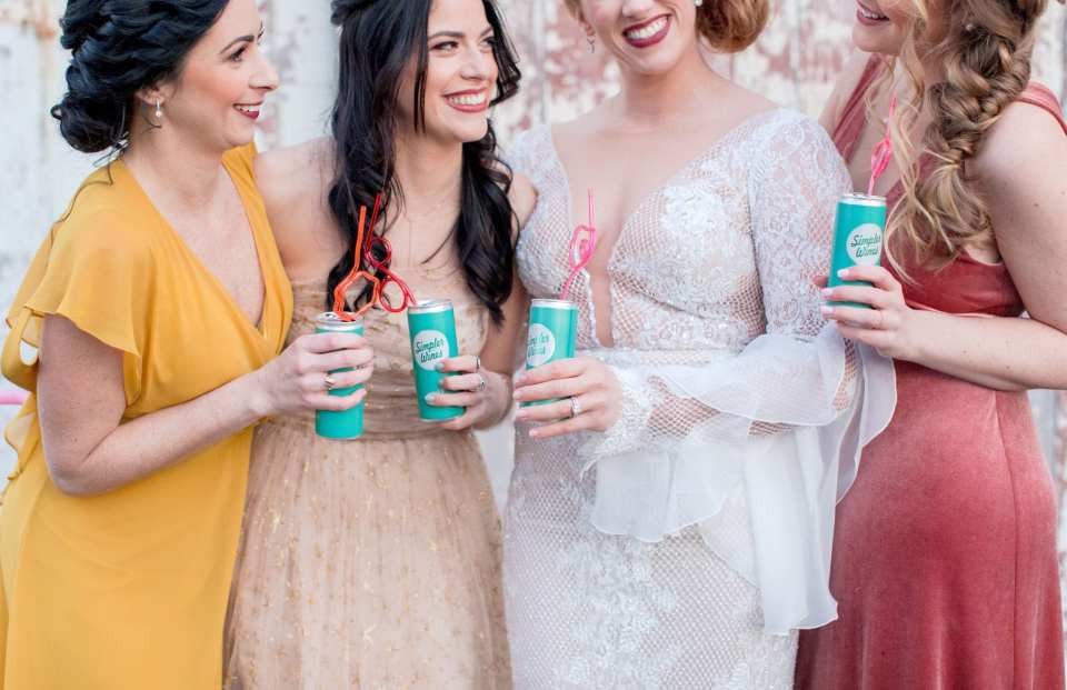 3/4 shot of bride in lace illusion gown and bridesmaids in three different coordinated gowns sipping on wine in a can with curly straws