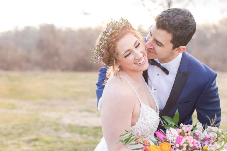 bride in spaghetti strap floral lace with crown of flowers in hair with her groom in a navy blue and black tuxedo