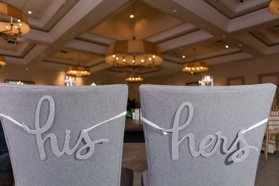 """photo of the bride and grooms chairs at the sweetheart table labelled with """"his and hers"""" silver glitter hanging signage"""