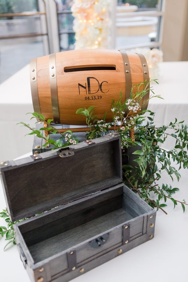 wedding detail shot of grey wooden wine box and brown barrel with slot of cards and their monogram and wedding date