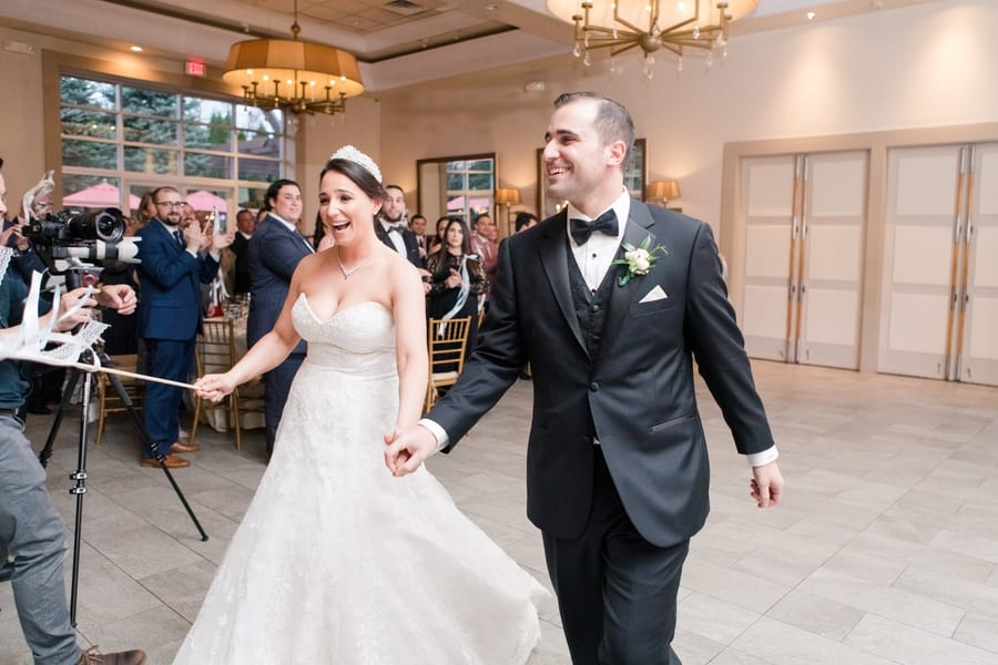 bride and groom smiling as they make their entrance together to the reception as husband and wife