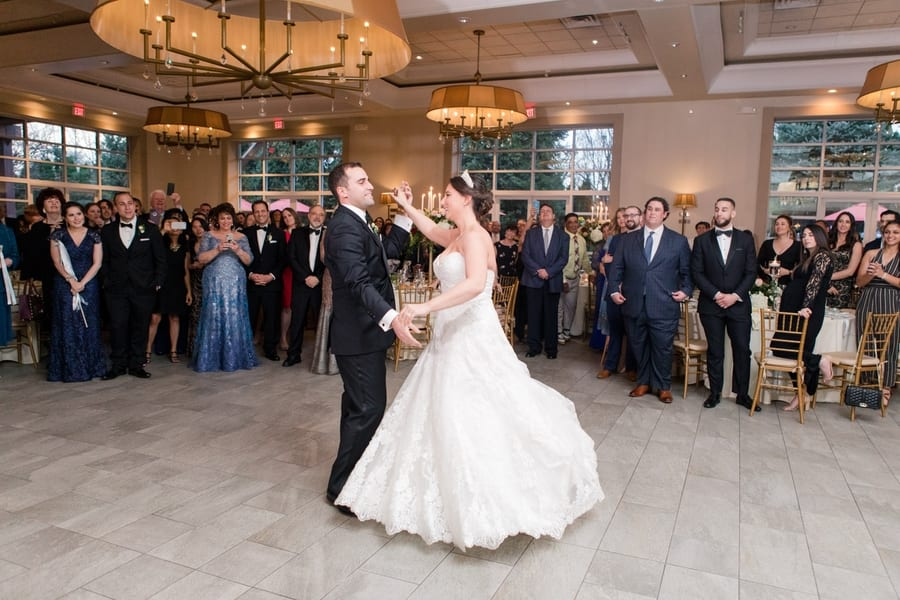 bride and groom during their first dance in front of guests