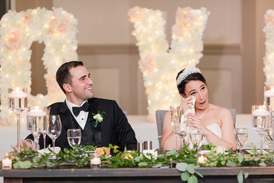 bride wipes away tears while groom laughs during speeches and toasts while sitting at the sweet heart table