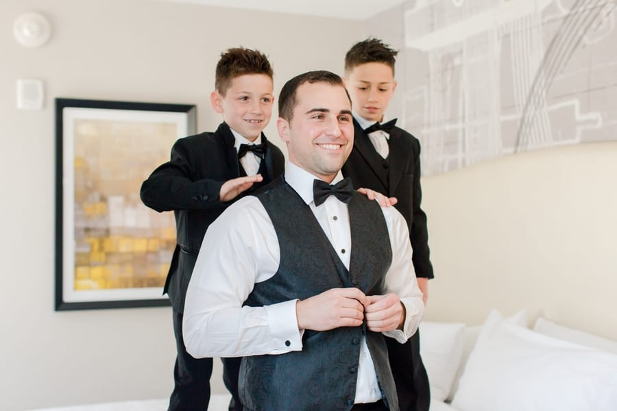 Groom smiling as he is helped into his tuxedo vest by his ring bearers