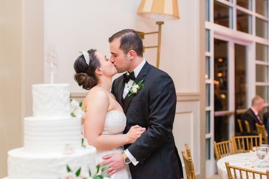 bride and groom formal kiss with the wedding cake