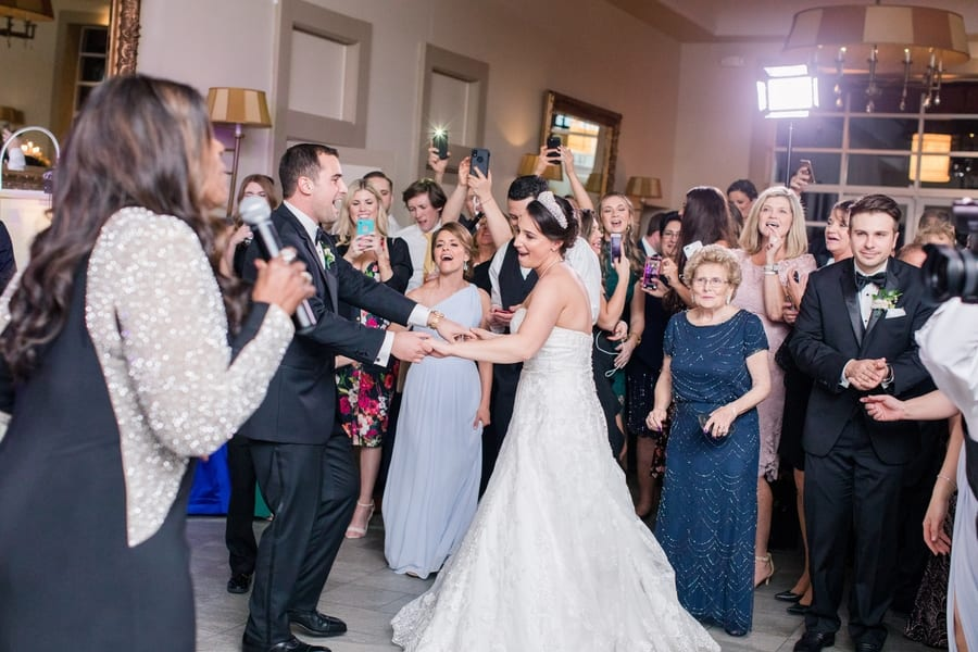 bride and groom dancing in front of guests while Gloria Gaynor sings