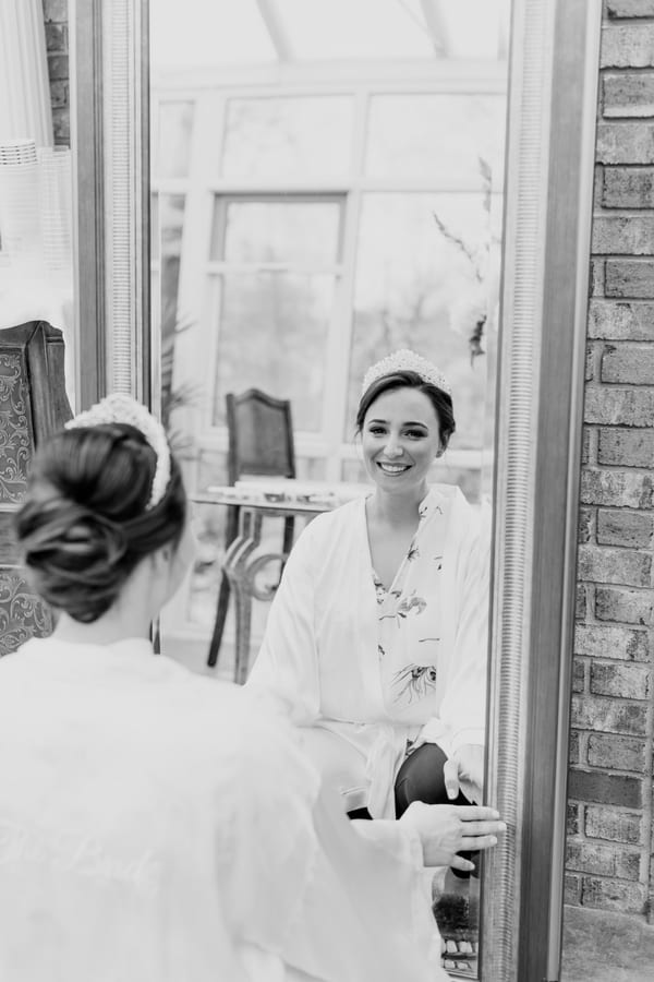 black and white photo of bride looking at her reflection in the mirror after having her makeup done before getting into her gown