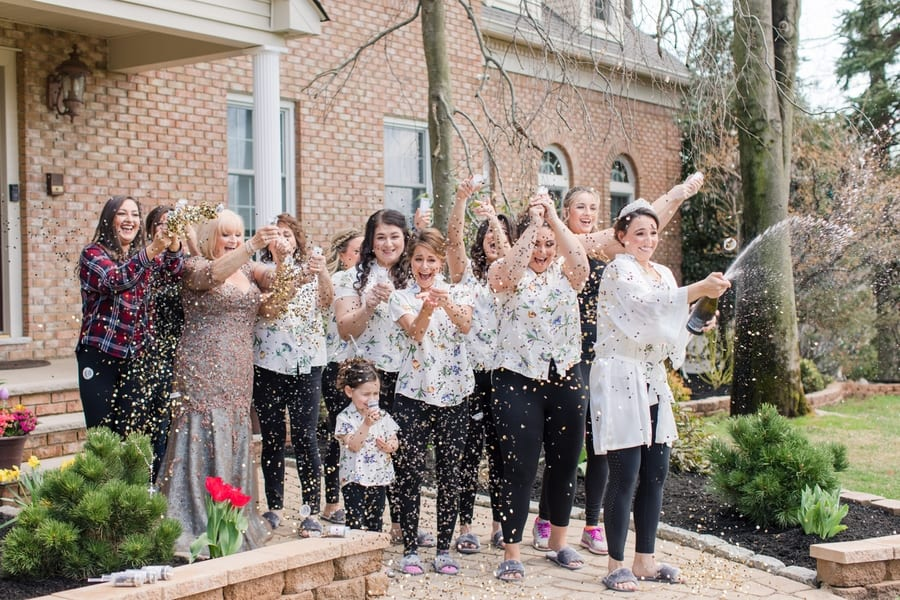 bride and her bridal party popping champagne and confetti outside before getting into their wedding attire