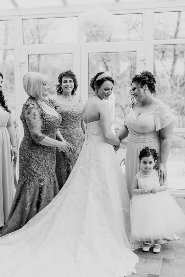 black and white photo of back of brides gown surrounded by her Mother an Mother of the groom