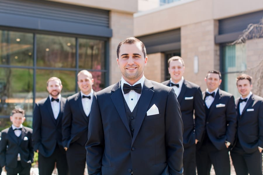 close up of groom standing out in front of groomsmen