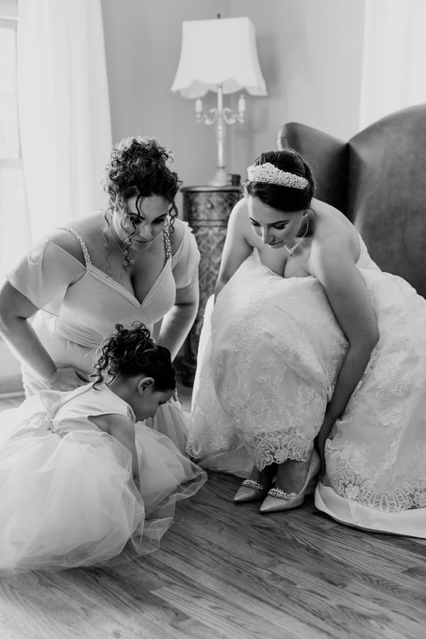 matron of honor and flower girl assist the bride in putting on her shoes