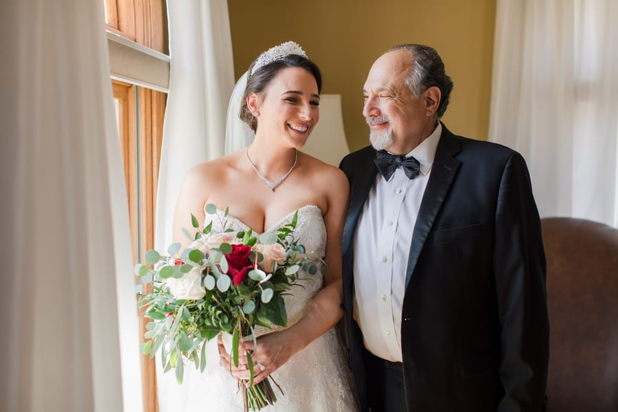 bride smiling with her father by a bright window in the bridal suite