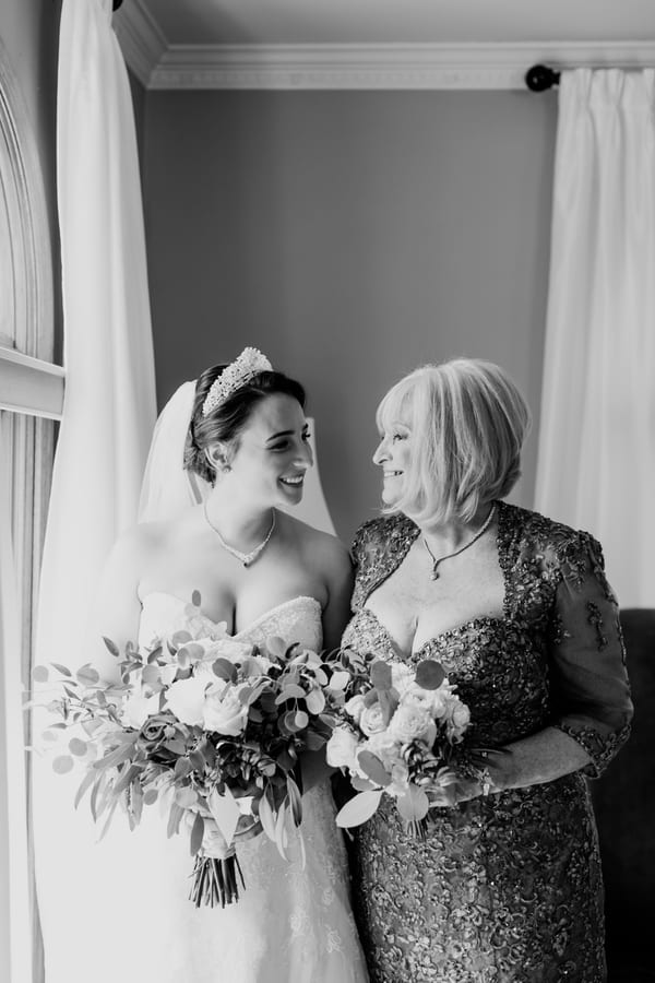 black and white photo of bride looking at her Mom and her Mom looking at her