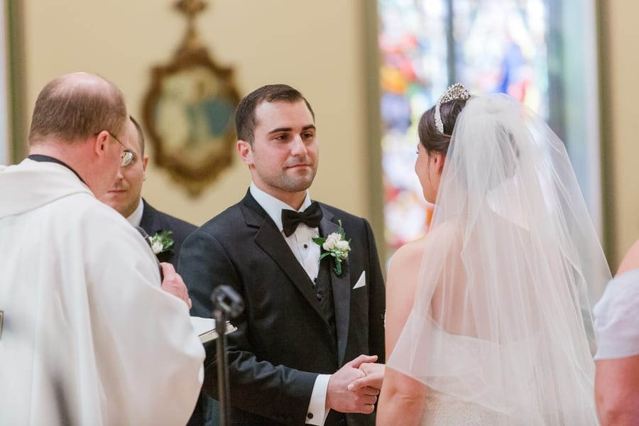 groom looking his bride while they take their wedding vows