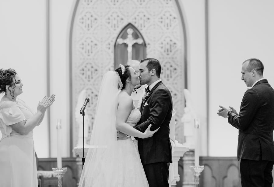 black and white photo of bride and groom having their first kiss as husband and wife, with her Maid of Honor and his best man on either side of the couple