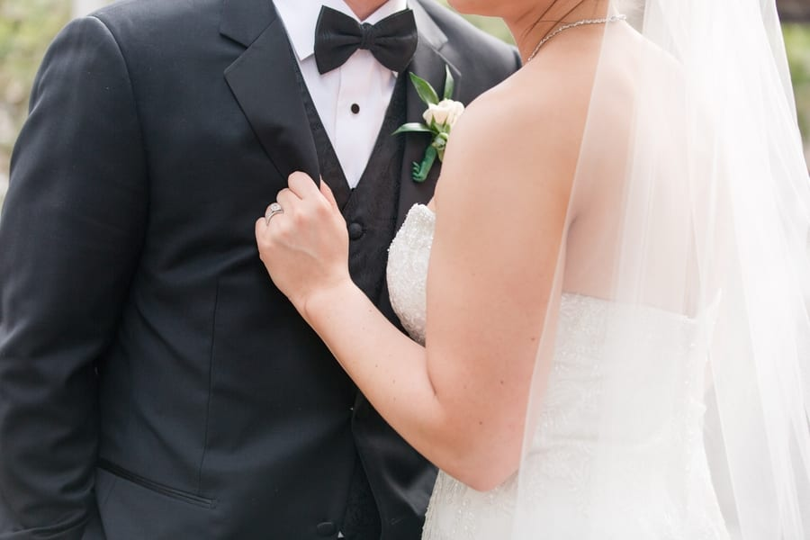 1/2 shot of bride holding onto grooms tuxedo lapel, focus on the hand, no faces in the photograph