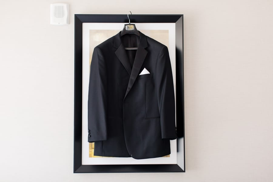 grooms tuxedo jacket displayed on a black framed print on a light grey wall