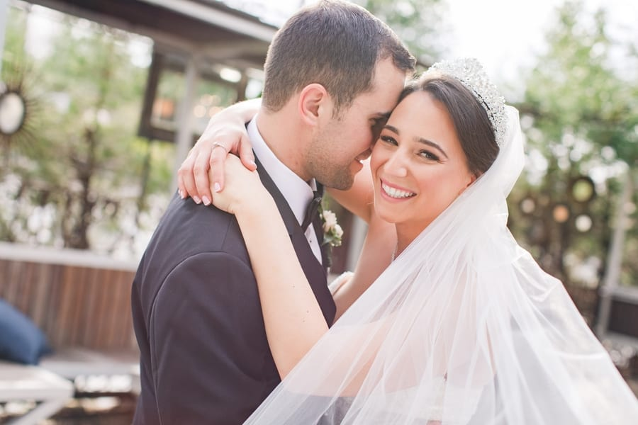 photo outdoors with bride wrapping her arms around her groom, with her veil wrapped around both of them