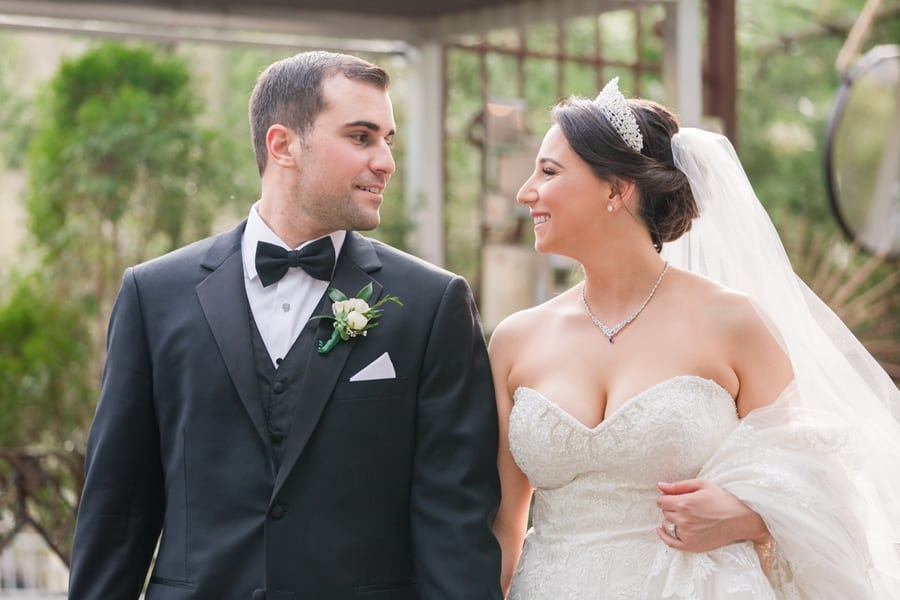 bride and groom smiling at each other while walking around the grounds of the Stone House