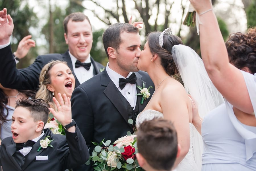 close up of bride and groom kissing while the wedding party cheers them on