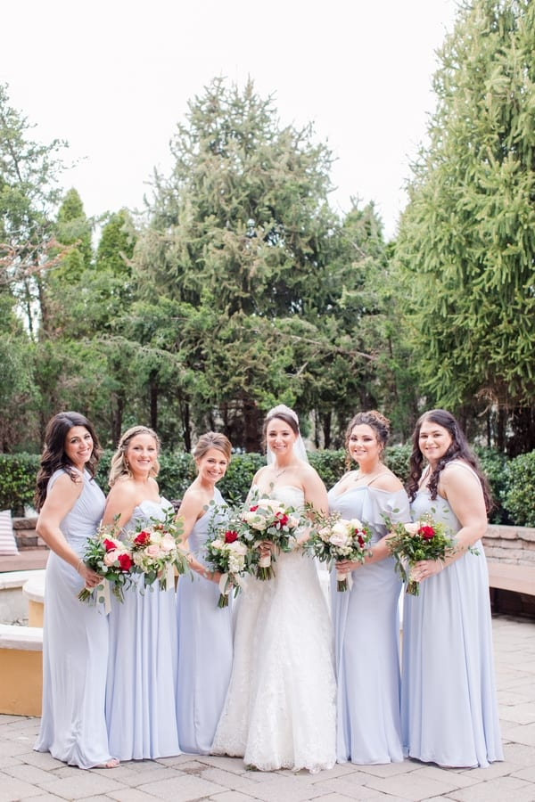 bride poses with her bridesmaids while they all hold their floral bouqets