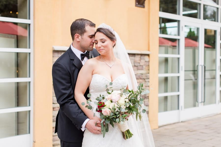 portrait of bride and groom closing their eyes while she holds her bouquet, all in front of the Stone House