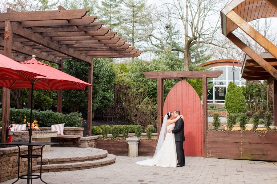 bride and groom kissing outside the Stone House on brick patio with fire pit and red accessories