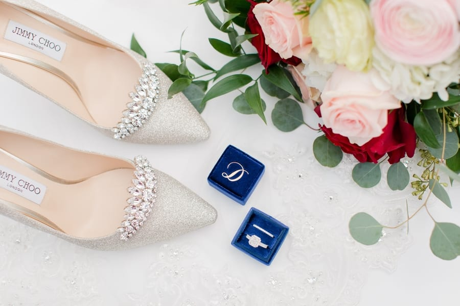 detail photo of brides Jimmy Choo rhinestone and glitter heels, the bridal bouquet of bus and red roses with white and cream accent florals and greenery, and her square diamond engagement ring and diamond wedding band in a blue ring box