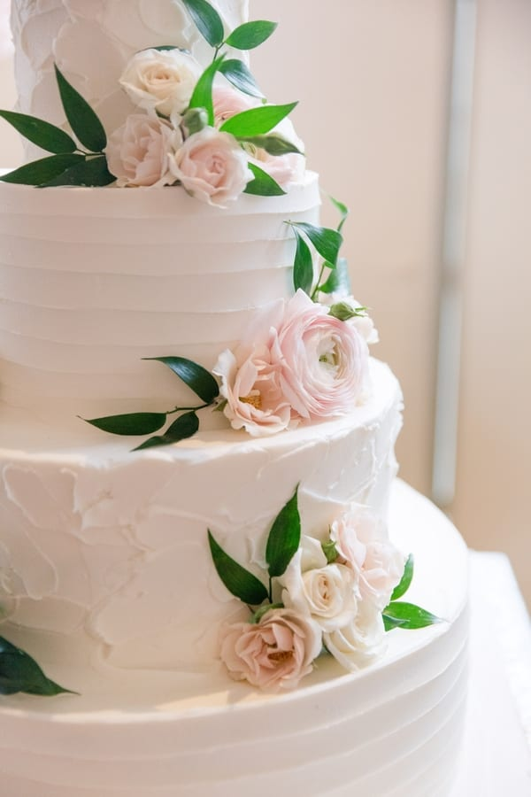 four tier whit wedding cake with two different frosting patterns with fresh blush florals scattered throughout the tiers