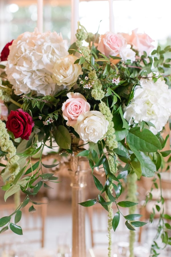 reception florals of blush, red and cream roses, white hydrangea and four white taper candles in the center, all surrounded by greenery