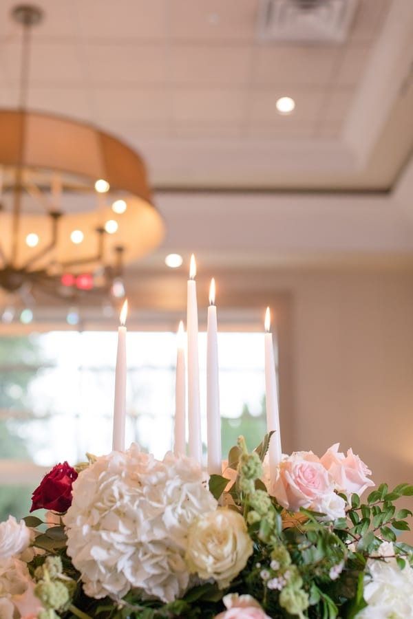 reception florals of blush, red and cream roses, white hydrangea and four white taper candles in the center