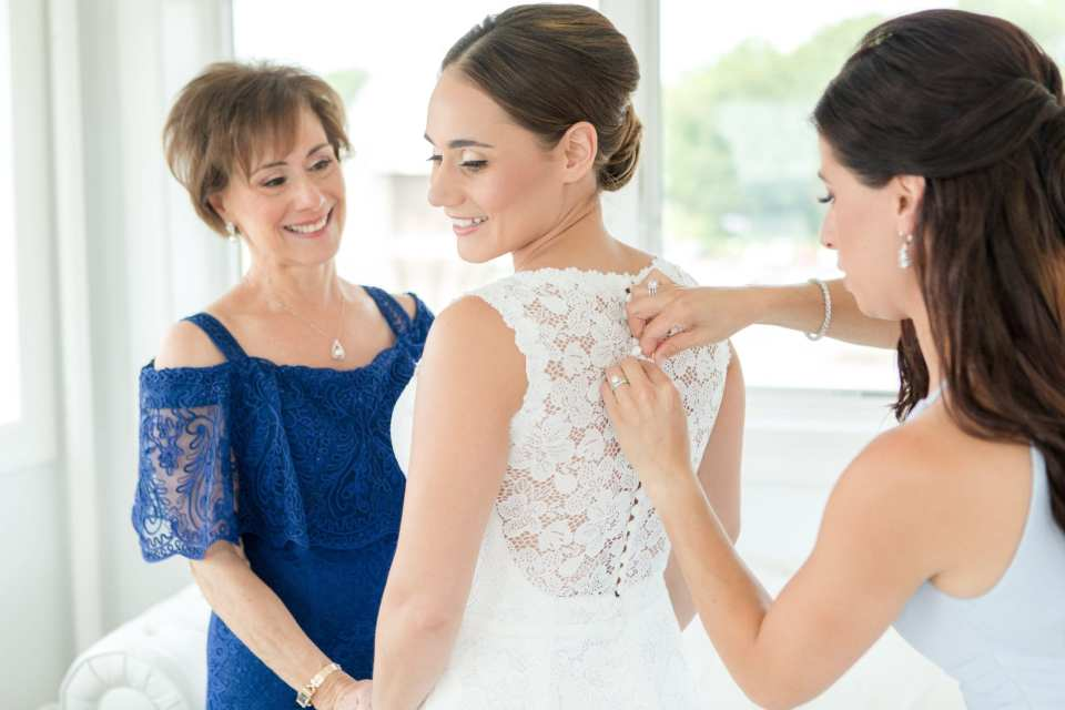 photo of bride from behind. mother in navy blue off the shoulder lace gown holding her hands in front, sister in light blue Watters gown behind her, buttoning her lace gown