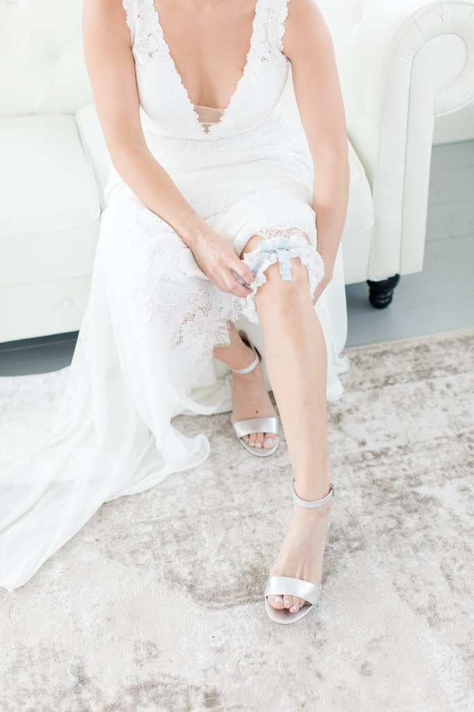 bride in v-neck gown by Pronovias putting on her family heirloom garter