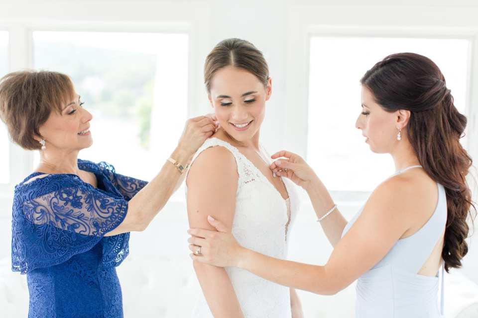 bride being helped with putting on her family heirloom necklace with her mother behind her and her sister in front.