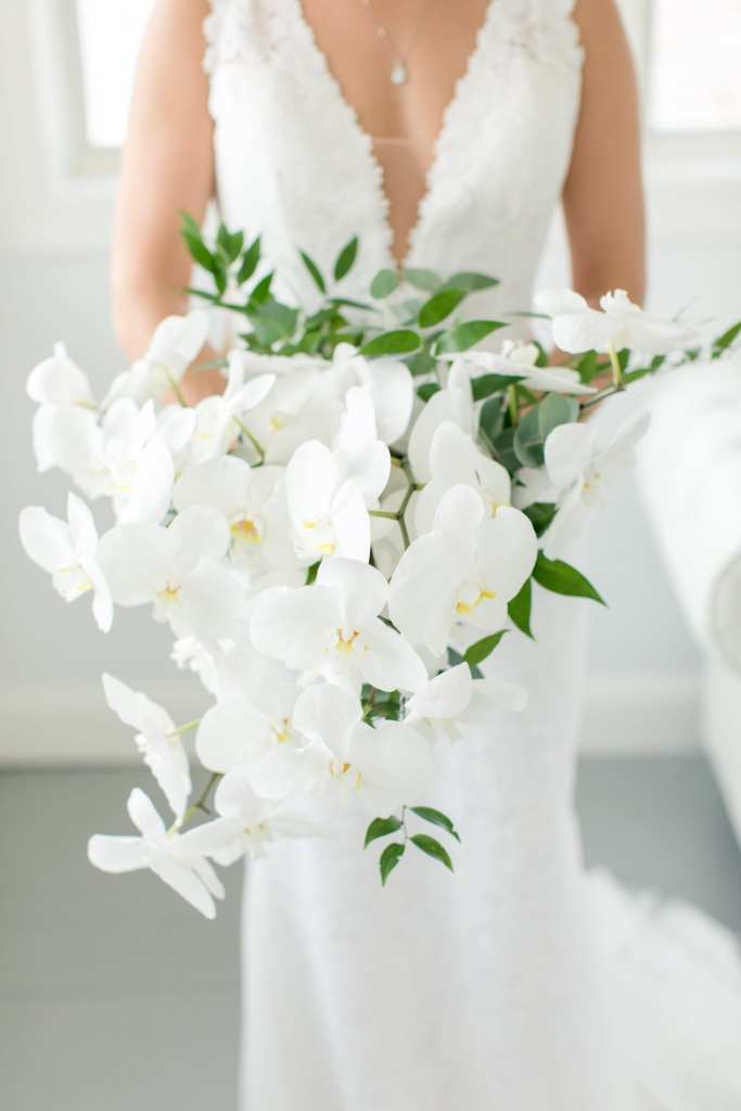 Focus on the brides white orchid cascading bouquet by From Peonies to Paint Chips