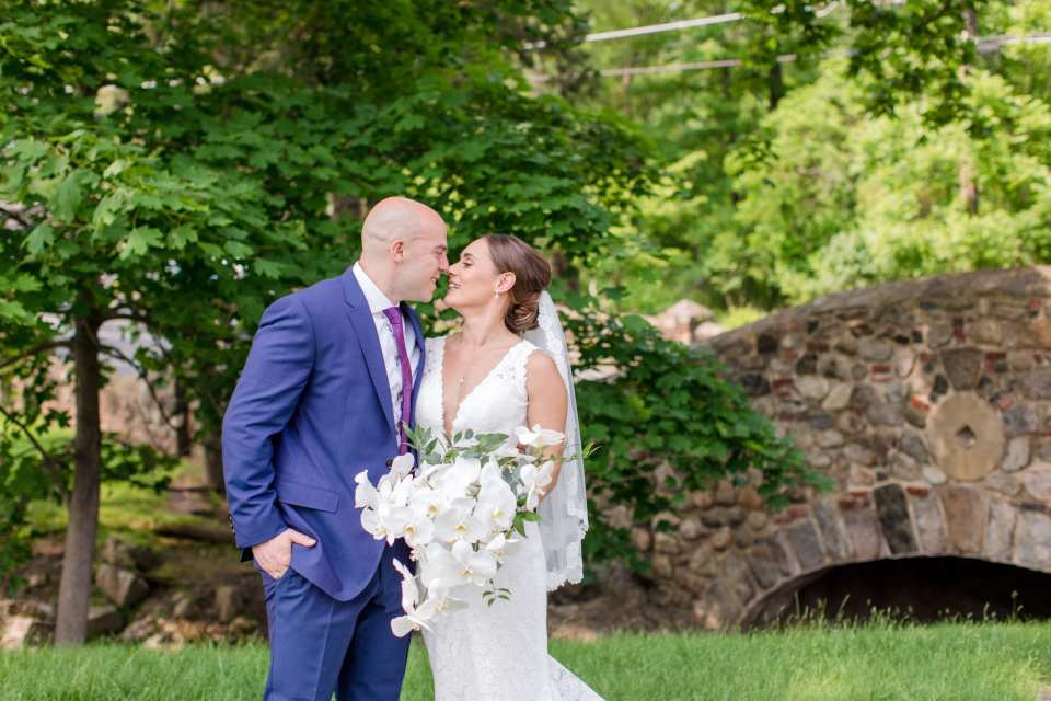 Bride in v-neck lace gown by Pronovias, groom in navy blue suit by Jos. A. Banks, holding one another behind their backs outdoors, with brick bridge in background