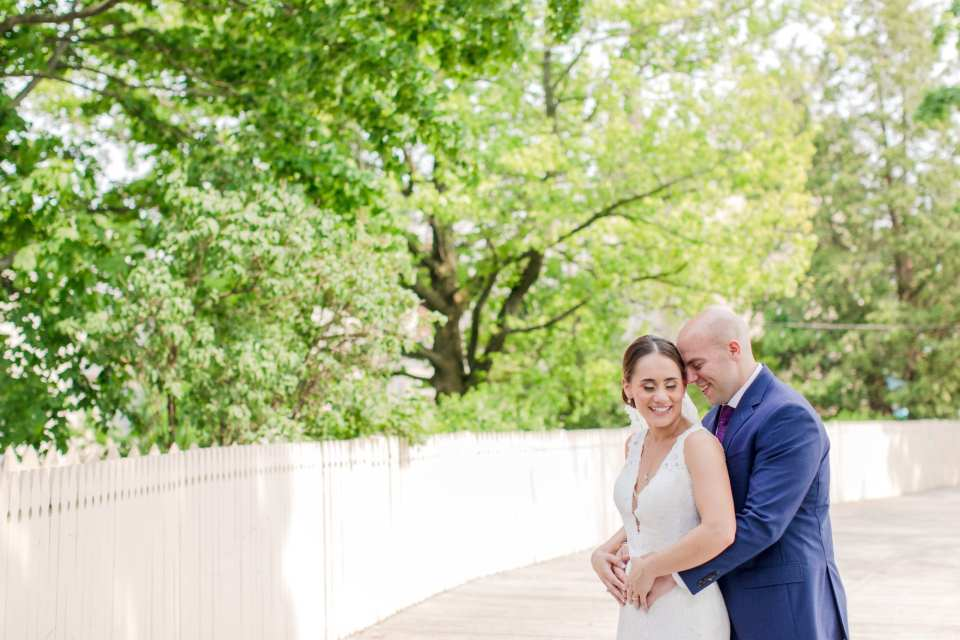 Bride in her Pronovias gown looking down while her groom in Jos. A. Banks wraps his arms around her waist from behind in an outdoor portrait with white picket fence and lush greenery