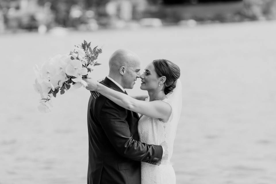 black and white photo of the bride and groom embracing one another, noses touching, with lake in background