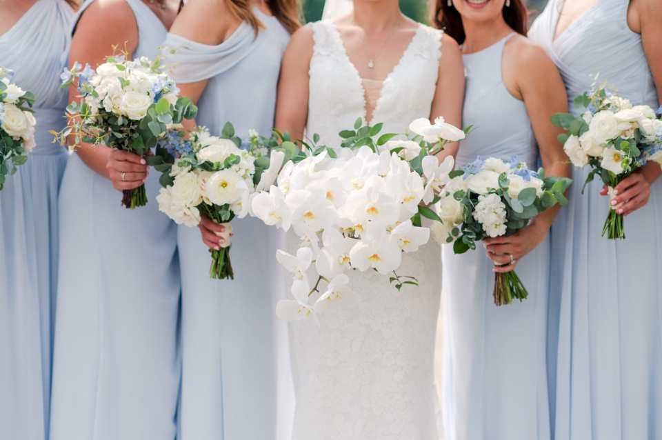 photo of the bride in v-neck lace gown by Pronovias surrounded by her bridal party in light blue floor length gowns by Watters, photo focusing in on their waists and floral bouquets