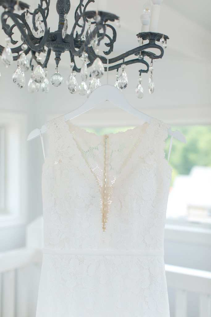 brides white lace gown by Pronovias hanging from a black wrought iron chandelier with crystals dripping off of it