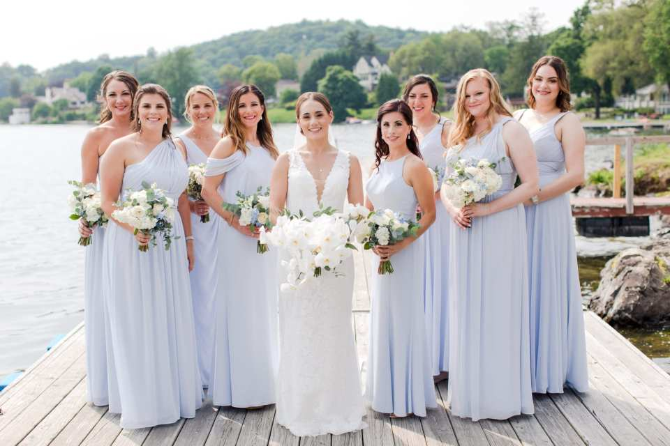 photo outdoors on the dock of the Lake Mohawk Country Club, of the bride in v-neck lace gown by Pronovias surrounded by her bridal party in light blue floor length gowns by Watters